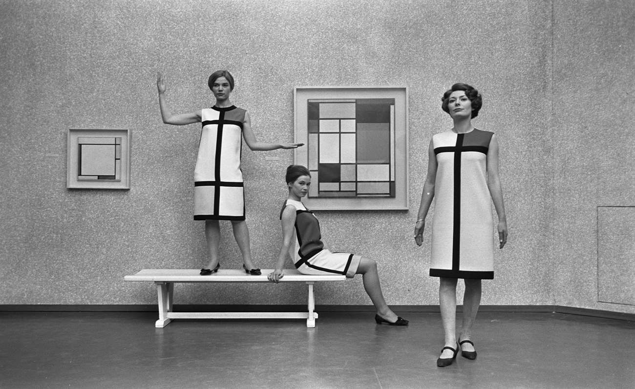 """Three """"Homage to Piet Mondrian"""" cocktail dresses, worn by models posing in front of Composition with Red, Yellow, Blue, and Black (1921), Musée municipal de la Haye, January 12, 1966 ©Yves Saint Laurent - photo Eric Koch - Nationaal Archief"""